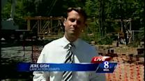 Crews rebuild covered bridge washed away by floodwaters