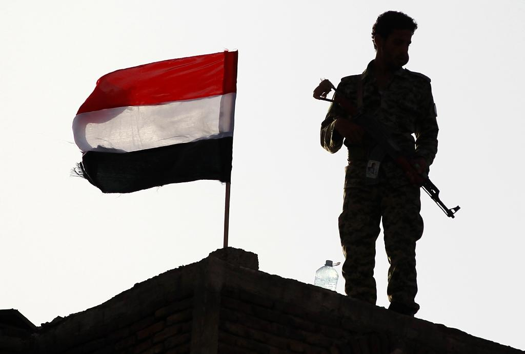 An armed Yemeni Shiite Huthi rebel stands next to a national flag in the capital Sanaa on September 21, 2015 (AFP Photo/Mohammed Huwais)
