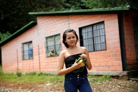 """Juany Iznaga, holding mangoes and other tropical fruits called """"Mamones,"""" poses for a picture next to her house in La Fria, Venezuela, June 2, 2016. REUTERS/Carlos Garcia Rawlins"""