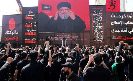 Lebanon's Hezbollah leader Sayyed Hassan Nasrallah gestures as he addresses his supporters via a screen