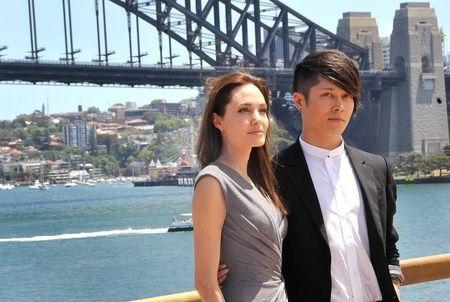 "Actress Angelina Jolie and cast member Miyavi pose in front of Sydney Harbor Bridge after a news conference for new film ""Unbroken"", November 18, 2014. REUTERS/Patrick Riviere"