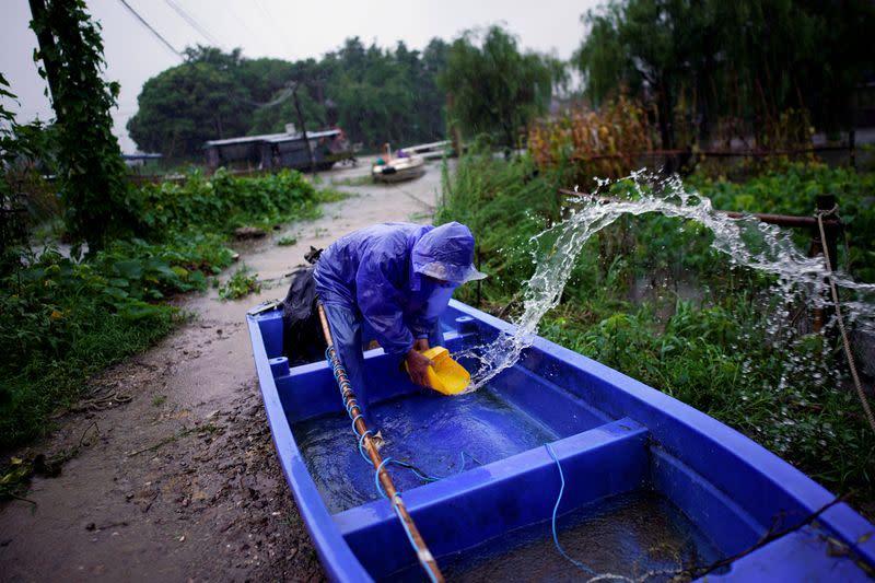 Heavy rains, floods in China strand dozens on rooftops, triggering landslides