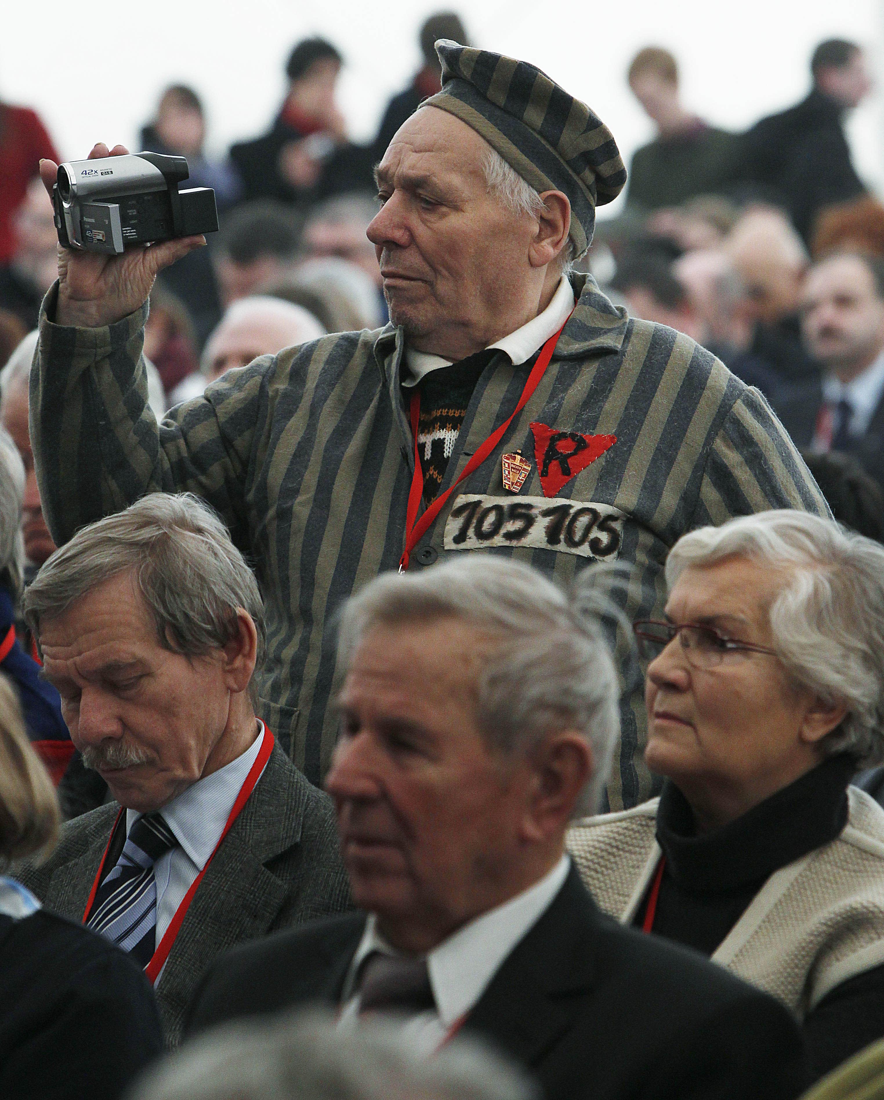 Un ex prisionero del campo de concentración de Auschwitz toma video de un acto con motivo del Día Internacional del Recuerdo del Holocausto en Oswiecim, Polonia, el domingo 27 de enero de 2013. (AP Foto/Czarek Sokolowski)