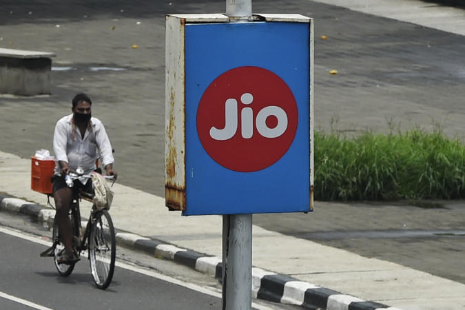 A cyclist passes by an advertising board of Reliance Jio, a digital platform owned by Indian businessman Mukesh Ambani's Reliance Industries, in Mumbai on June 19, 2020. - Ambani said on June 19 that his Reliance conglomerate is net debt free after raising more than $22 billion in a rights issue and selling stakes in its e-commerce unit to Facebook, Saudi Arabia's wealth fund and others. Asia's richest man after upending the Indian telecoms market, Ambani is attempting to do the same in e-commerce with Jio Platforms, taking on US giants Amazon and Walmart in the vast market of 1.3 billion consumers. (Photo by Punit PARANJPE / AFP) (Photo by PUNIT PARANJPE/AFP via Getty Images)