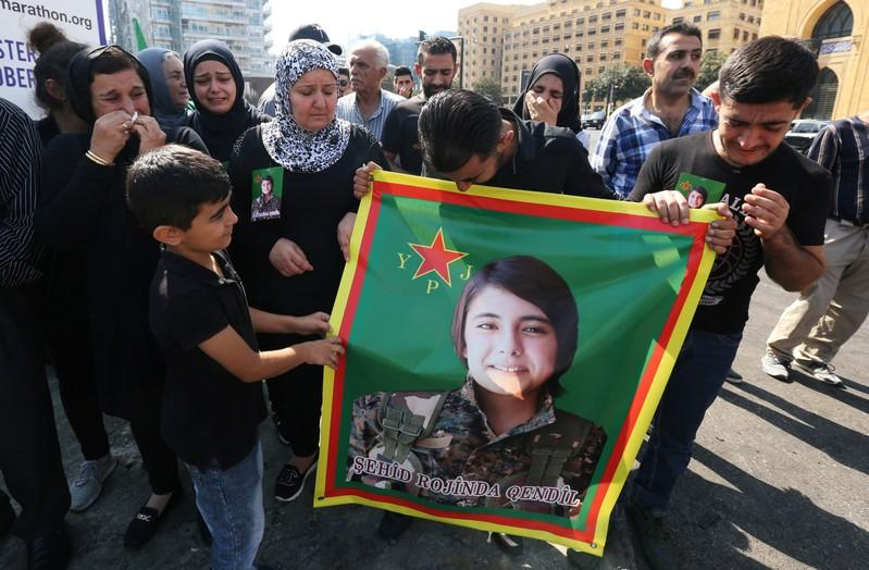 Kurds living in Lebanon react as they hold Hevrin Khalaf's picture, a Kurdish politician who was killed in Syria, during a protest against Turkey's military action in northeastern Syria
