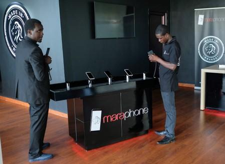 Workers display the Mara X and Mara Z smartphones during their launch by Rwanda's Mara Group in Kigali,