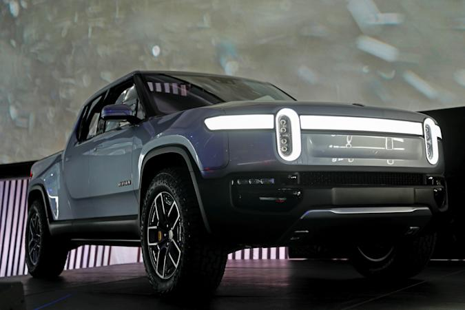 A Rivian EV pickup truck on display at an auto show, on stage by itself.