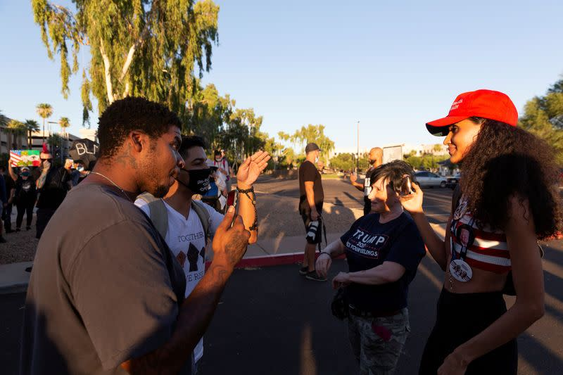 FILE PHOTO: Black Lives Matter protesters interact with protesters against restrictions to prevent the spread of the coronavirus disease (COVID-19) in Phoenix