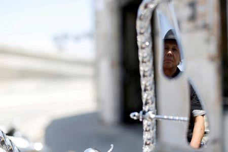 Manny Silva is reflected in the mirror of a low rider bicycle he customized, outside his bike shop in Compton, California U.S., June 3, 2016. Picture taken June 3, 2016. REUTERS/Mario Anzuoni