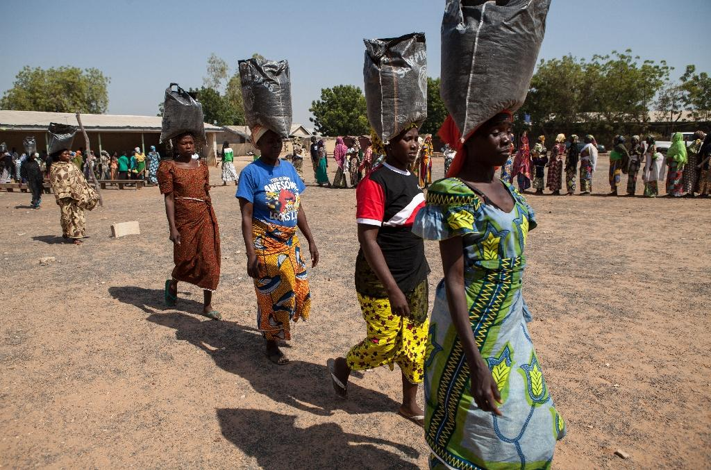 This photo taken on December 4, 2014 shows displaced women carrying sacks of food aid received during a distribution at the Cathedral of Yola, state capital of Adamawa (AFP Photo/Florian Plaucheur)