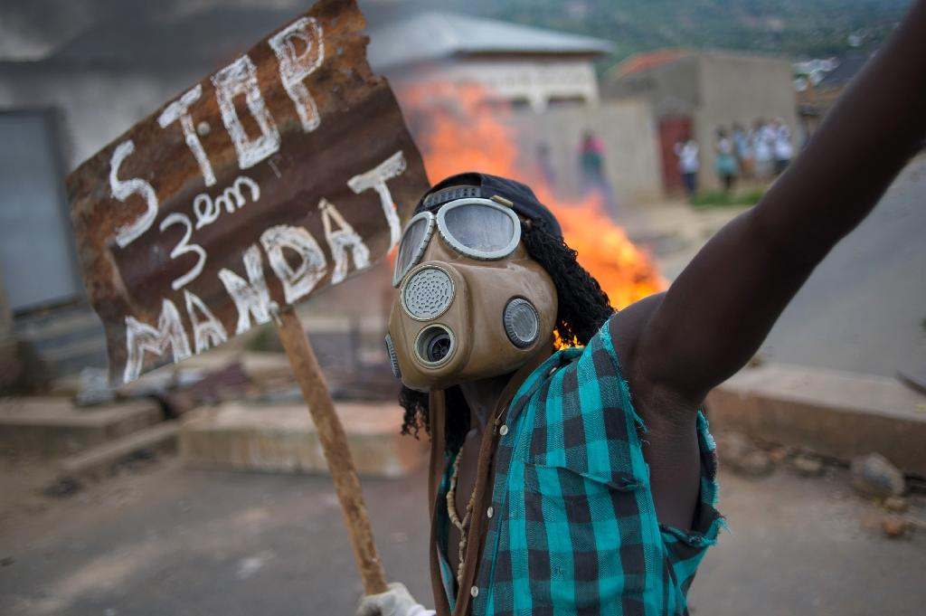 """A protester wearing a gas mask holds a sign reading """"Stop the third mandate"""" near a burning barricade in the Mugasa neighbourhood of Bujumbura on May 6, 2015 (AFP Photo/Phil Moore)"""