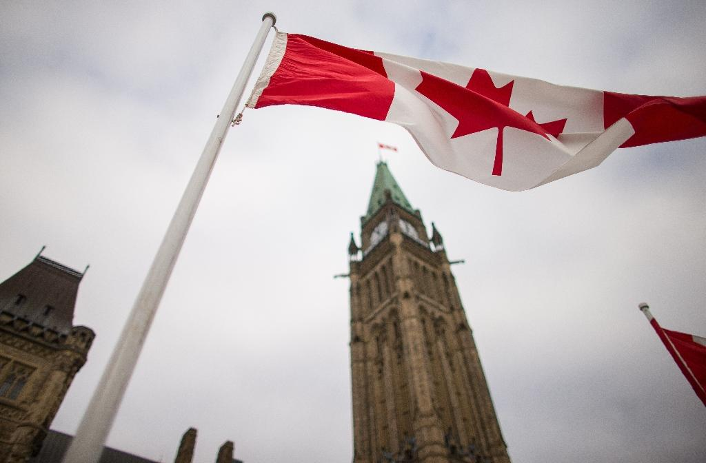 A Canadian flag flies in front of the peace tower on Parliament Hill in Ottawa, Canada