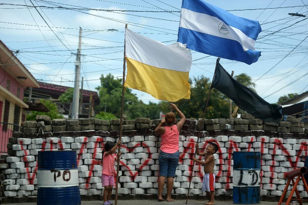A woman and children place a Nicaraguan, a Vatican and a black flag on a barricade at Monimbo neighbourhood in Masaya (AFP Photo/MARVIN RECINOS)