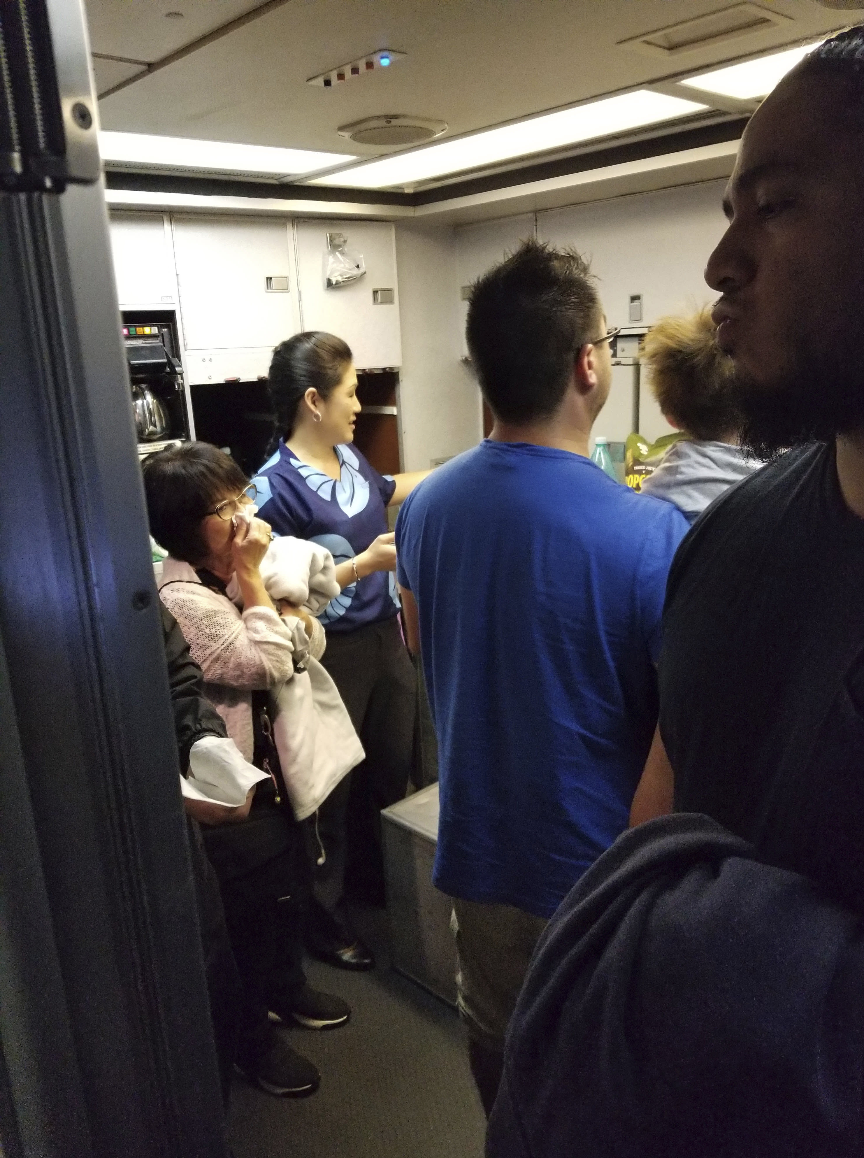 This Friday, Aug. 31, 2018 photo provided by Nicholas Andrade shows people gathered in a back galley on a Hawaiian Airlines flight from Oakland, Calif., to Kahului, Hawaii, after a can of pepper spray went off inside the plane. Twelve passengers and three flight attendants were treated for respiratory issues and released by emergency responders at the airport in Kahului, which is on the island of Maui. (Nicholas Andrade via AP)