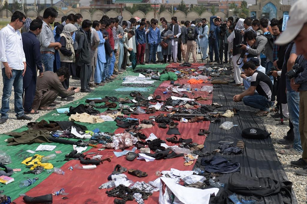 Relatives and friends inspect shoes and other belongings of those who were killed in the twin suicide attack, gathered on the ground at a mosque in Kabul on July 24, 2016 (AFP Photo/Shah Marai)