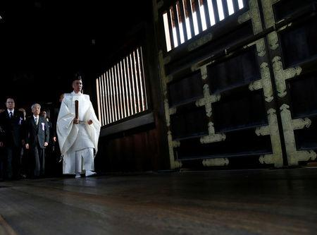 A group of lawmakers are led by a Shinto priest as they pay their respects at the Yasukuni Shrine in Tokyo