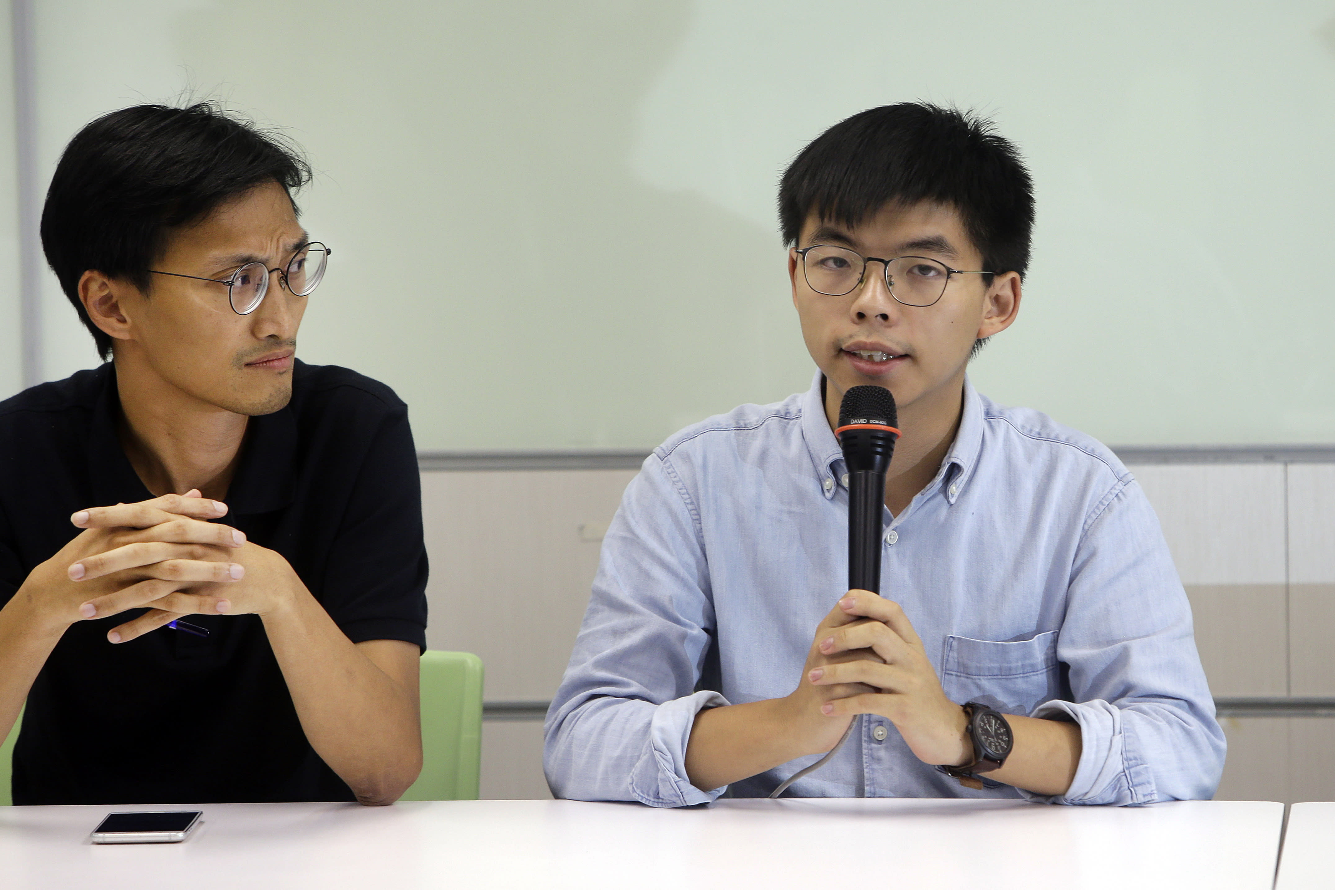 Hong Kong activist Joshua Wong, right, answers to the press after meeting with Taiwan Democratic Progressive Party (DPP) political leaders in Taipei, Taiwan, Tuesday, Sept. 3, 2019. Joshua Wong visited pro-democracy political leaders and joint forum during a two-days trip from Tuesday in Taiwan. (AP Photo/ Chiang Ying-ying)