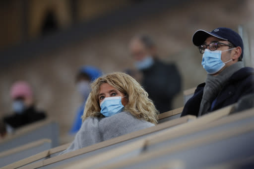 Spectators with face masks watch the first round match of the French Open tennis tournament between Belgium's David Goffin and Italy's Jannik Sinner at the Roland Garros stadium in Paris, France, Sunday, Sept. 27, 2020. (AP Photo/Christophe Ena)
