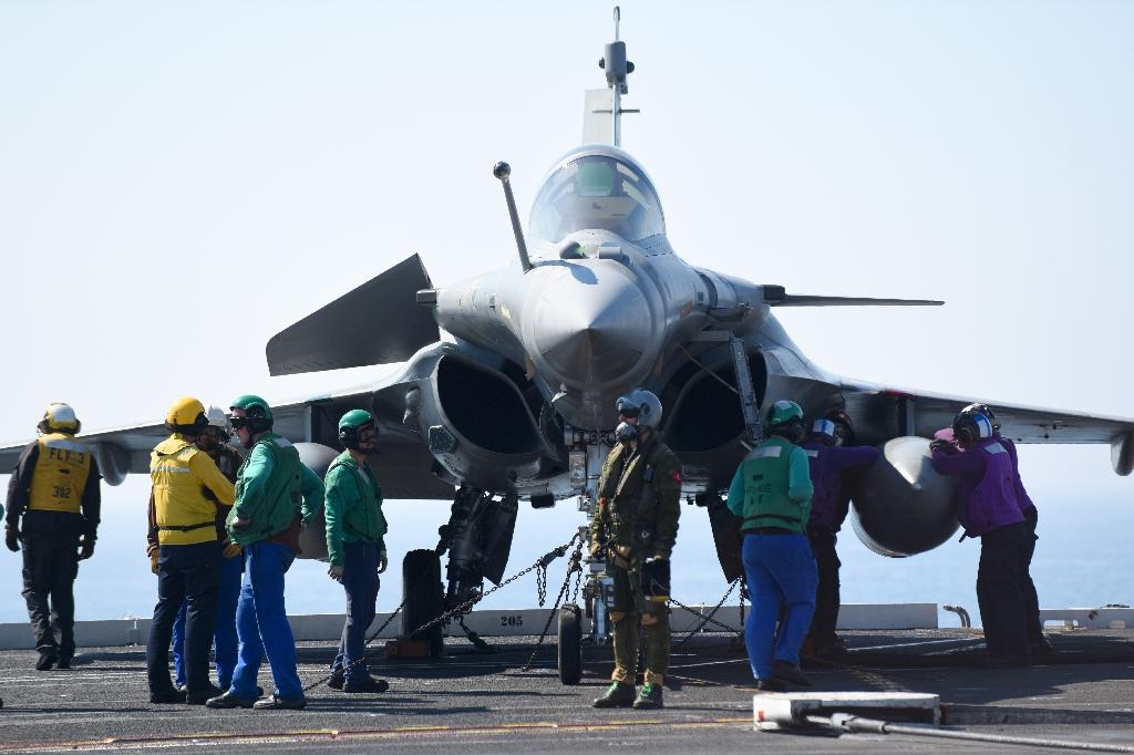French Navy personnel gather around a French pilot and his Rafale jet, one of 12 assigned to the US training mission, after it landed on the USS George H.W. Bush aircraft carrier (AFP Photo/Eric BARADAT)