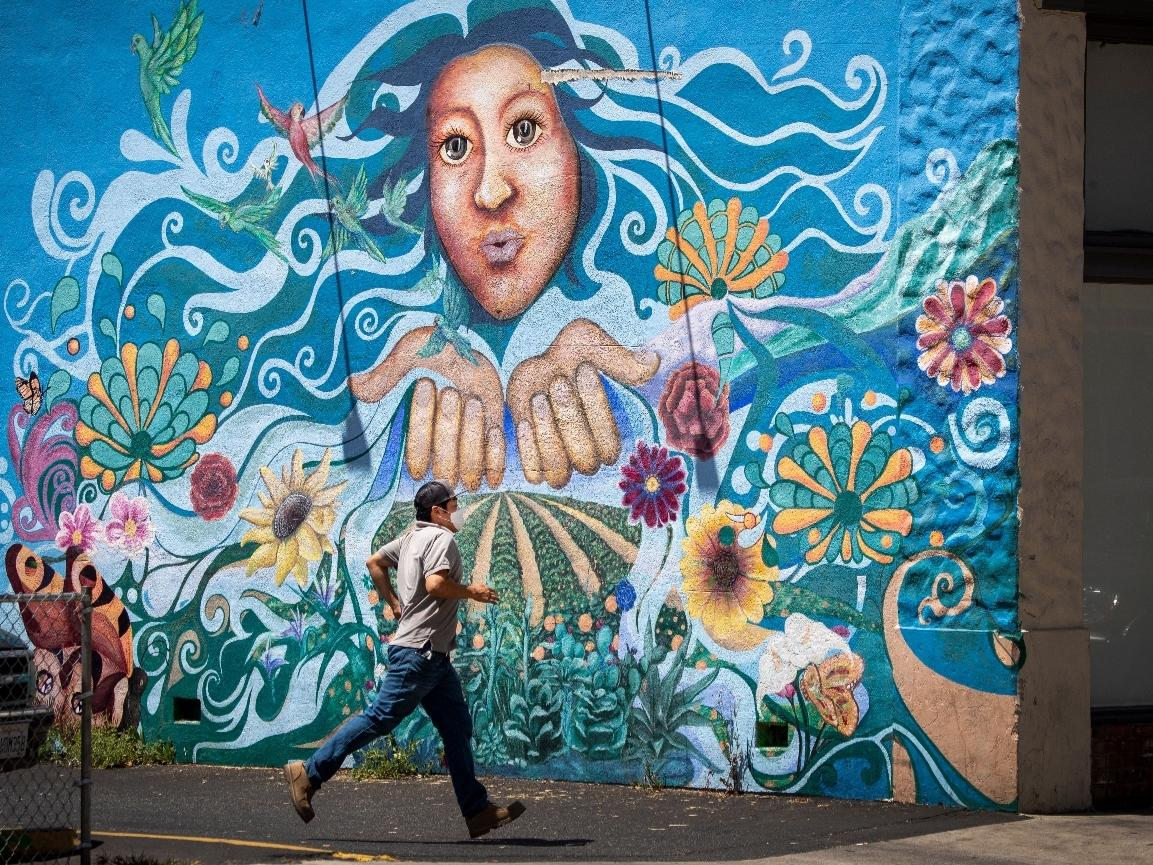 A pedestrian wearing a mask runs past a mural in downtown Santa Ana on Tuesday, July 7, 2020.