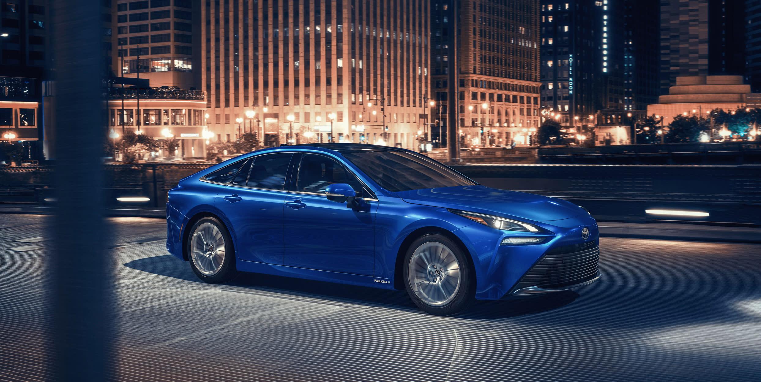 The 2021 Toyota Mirai fuel-cell vehicle cruising through a city environment.