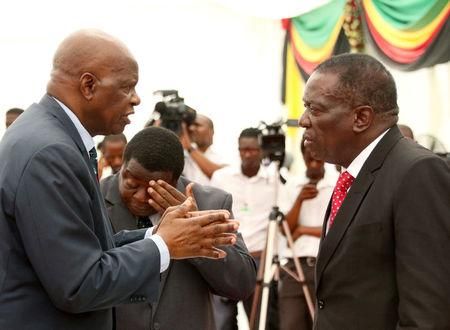 Zimbabwean President Emmerson Mnangagwa confers with Finance Minister Patrick Chinamasa at State House in Harare