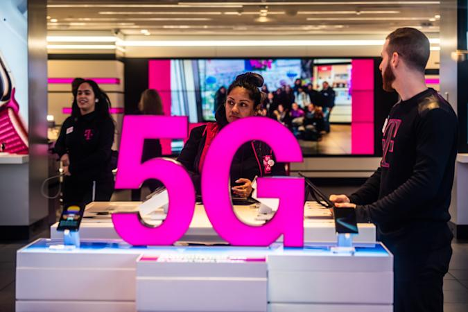NEW YORK CITY, UNITED STATES - 2020/02/20: Customers at a T-Mobile store, with 5G signage. (Photo Illustration by Alex Tai/SOPA Images/LightRocket via Getty Images)