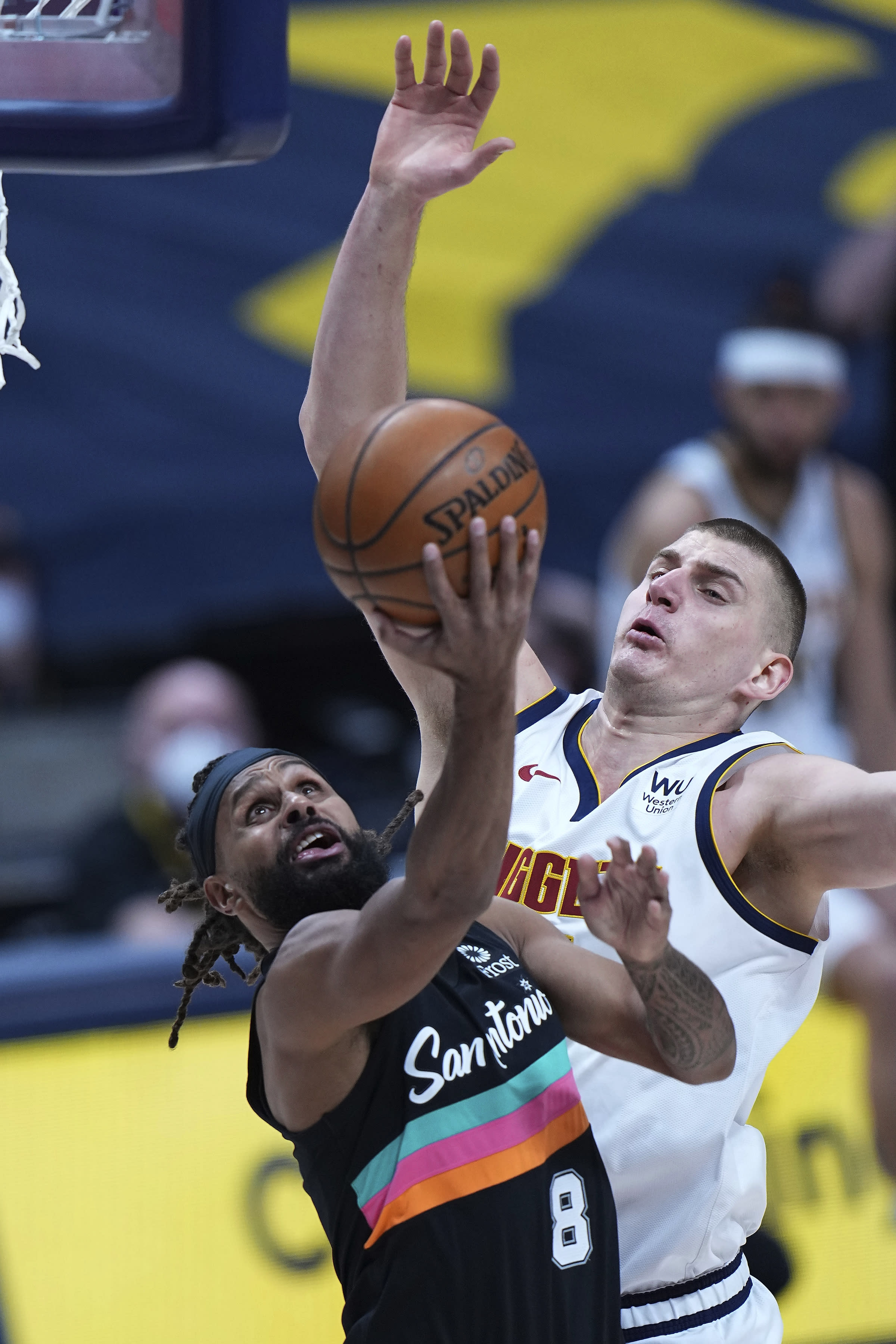 San Antonio Spurs guard Patty Mills (8) shoots against Denver Nuggets center Nikola Jokic during the first quarter of an NBA basketball game Wednesday, April 7, 2021, in Denver. (AP Photo/Jack Dempsey)
