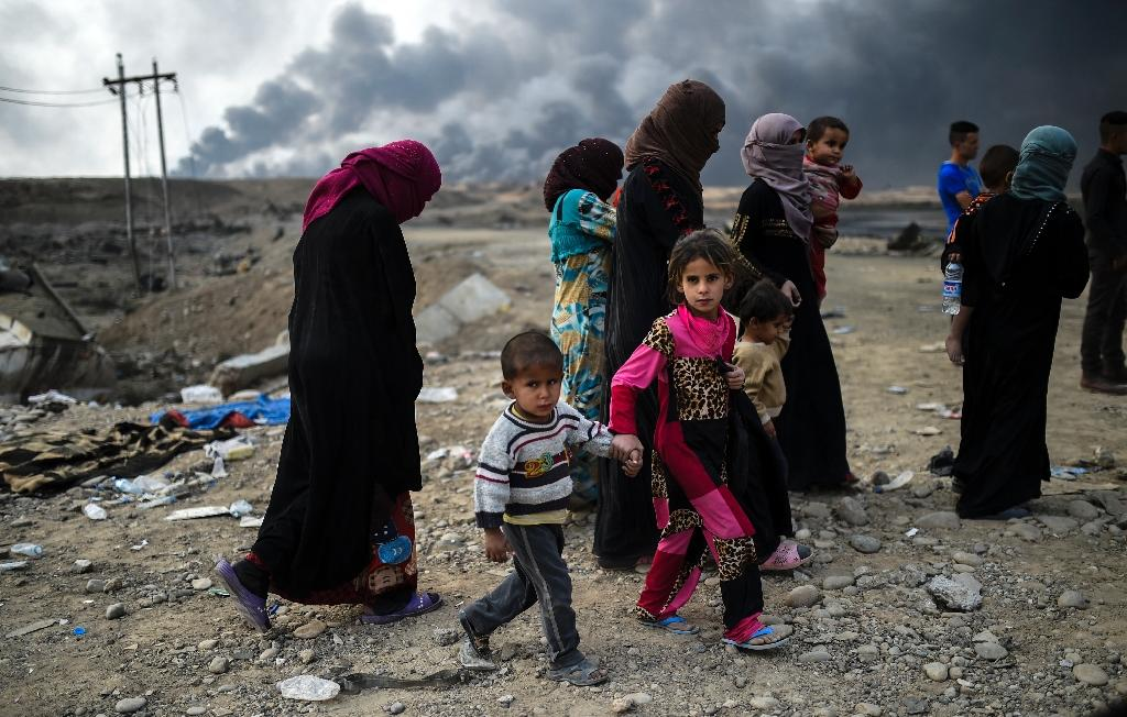 Iraqi families who were displaced by the ongoing operation by Iraqi forces against jihadists of the Islamic State group to retake the city of Mosul, are seen gathering in an area near Qayyarah on October 24, 2016 (AFP Photo/Bulent Kilic)