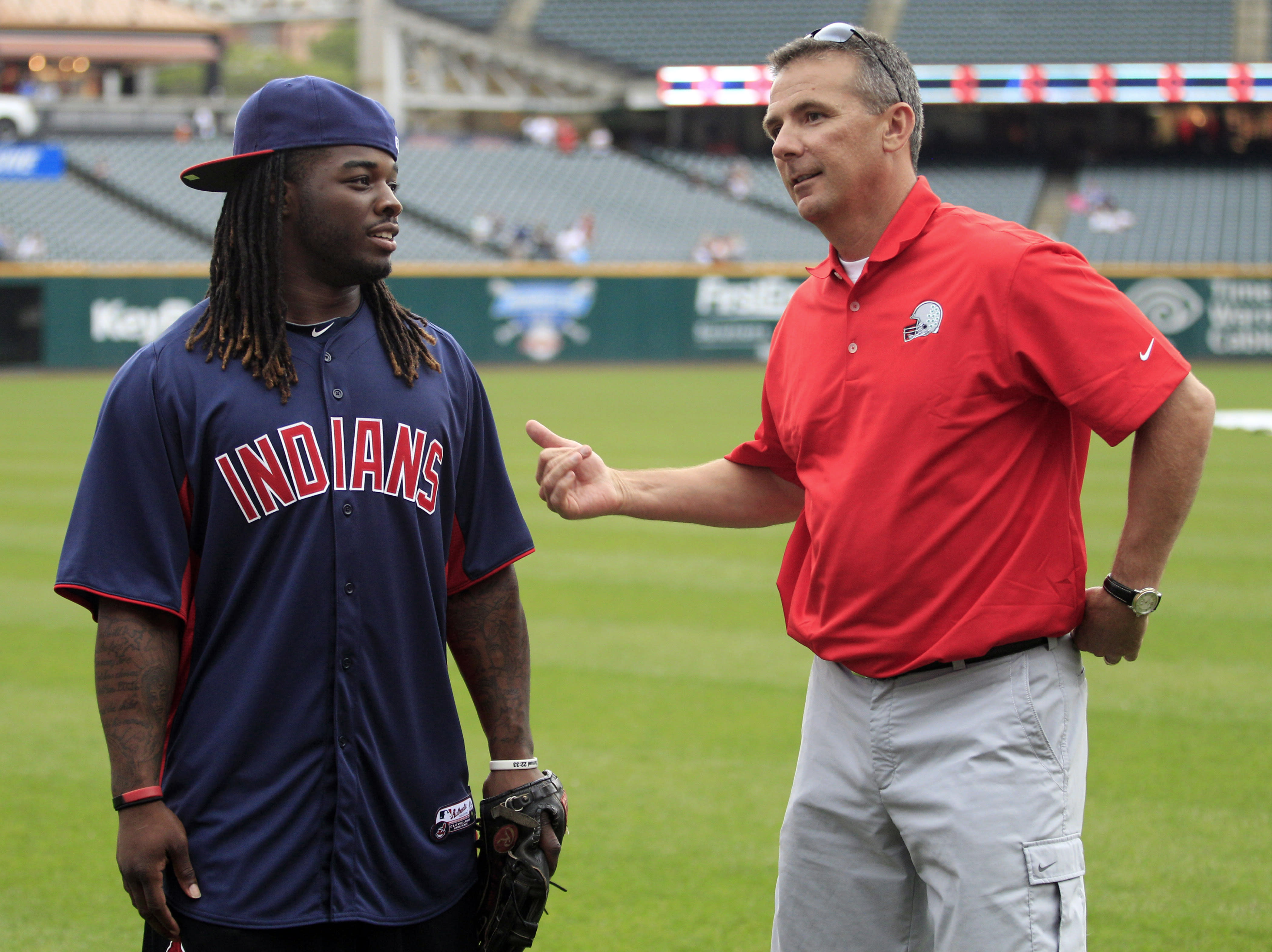 Cleveland Browns running back Trent Richardson, left, talks with Ohio State football coach Urban Meyer before the Cleveland Indians play the Cincinnati Reds in a baseball game, Monday, June 18, 2012, in Cleveland. (AP Photo/Tony Dejak)