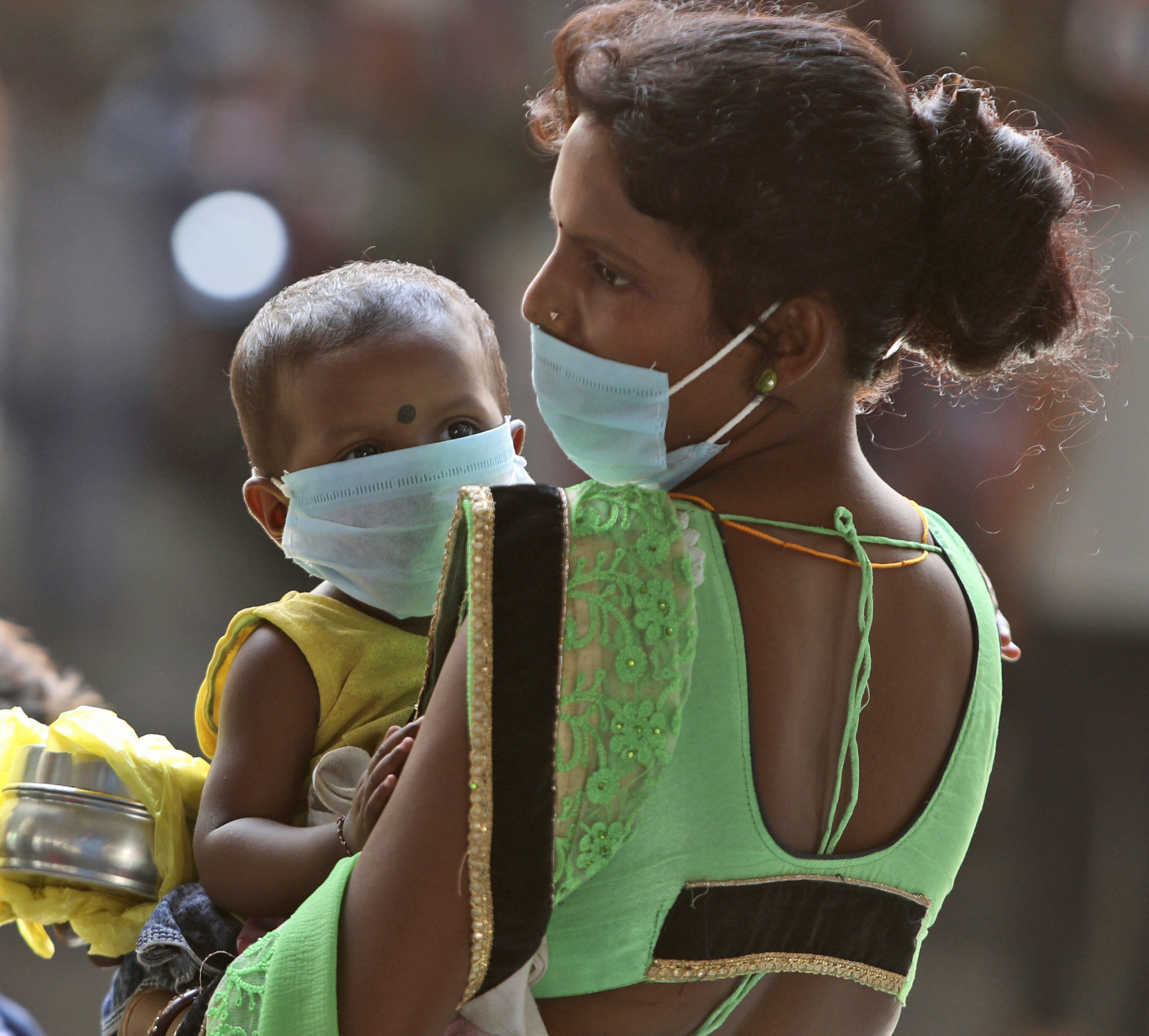 A woman wearing a face mask as a precaution against the coronavirus carries a child and waits for transportation at a bus station in Jammu, India, Friday, Sept. 11, 2020. Results of India's first nationwide study of prevailing coronavirus infections has found that for every confirmed case detected in May, authorities were missing between 82 and 130 others. At the time, India had confirmed around 35,000 cases and over 1,000 deaths. The study released Thursday shows 6.4 million people were likely infected. (AP Photo/Channi Anand)