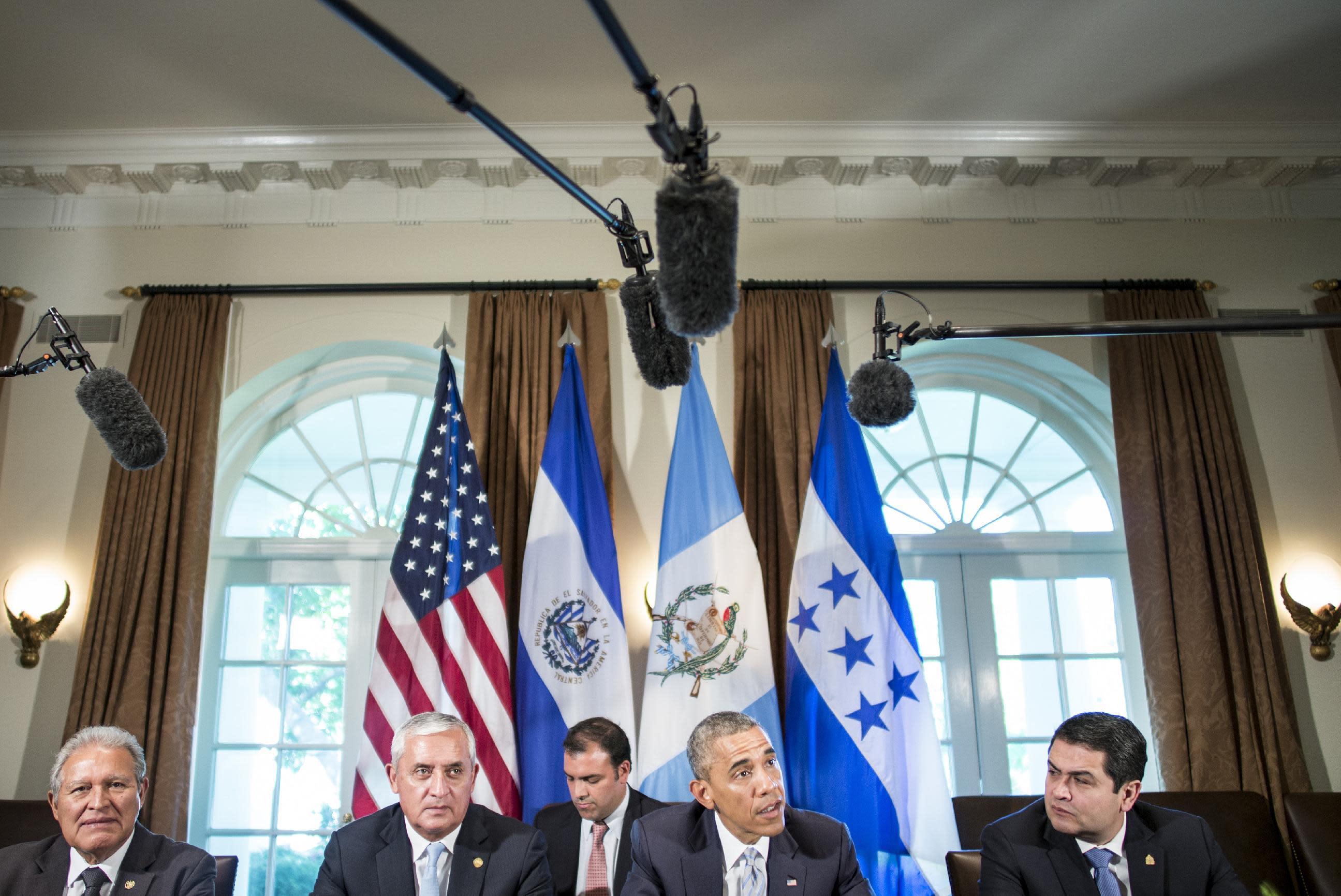 President of El Salvador Salvador Sanchez Ceren (L), President of Guatemala Otto Perez Molina (2-L) and President of Honduras Juan Orlando Hernandez (R) listen while US President Barack Obama speaks to the press on July 25, 2014 in Washington (AFP Photo/Brendan Smialowski)