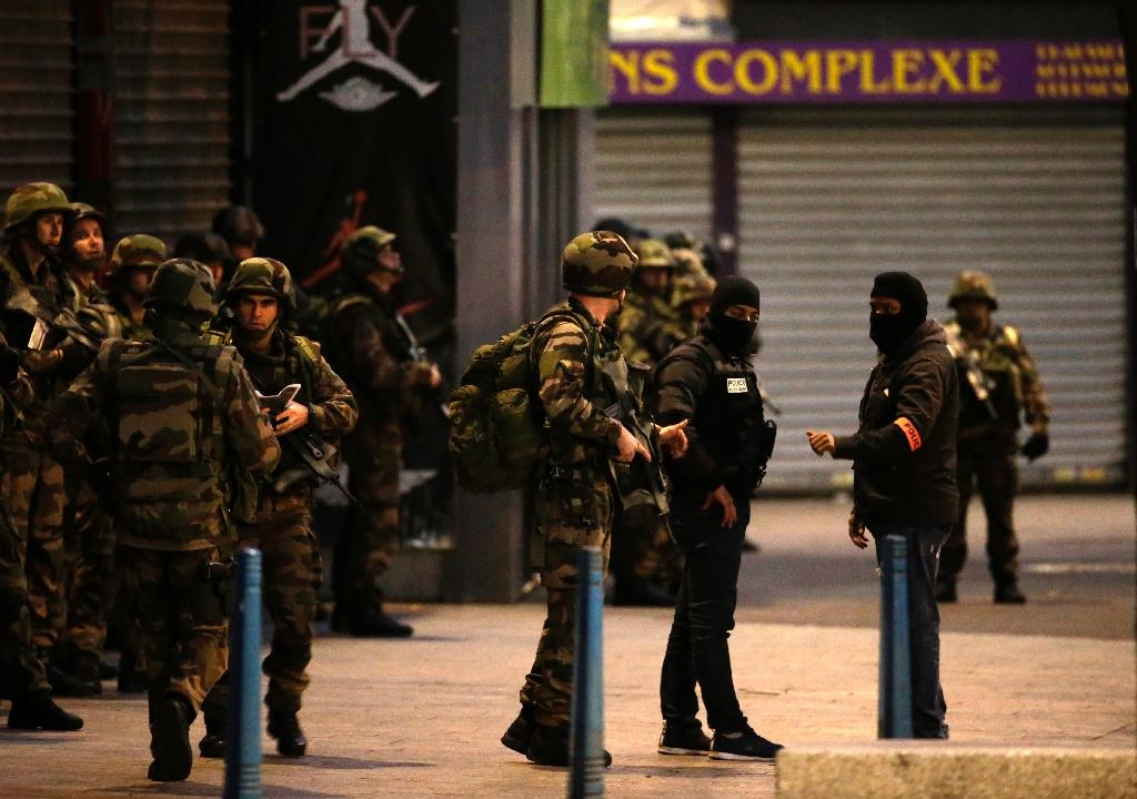 French soldiers and members of police special forces stand guard in the northern Paris suburb of Saint-Denis city center, on November 18, 2015, during an anti-terror operation (AFP Photo/Kenzo Tribouillard)