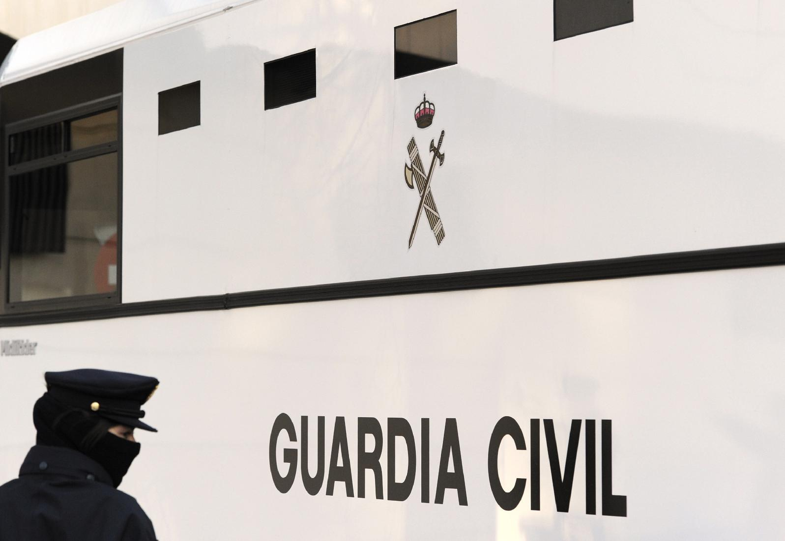 An officer of Spain's Guardia Civil stands next to a van carrying prisoners at Madrid's High Court on January 27, 2010