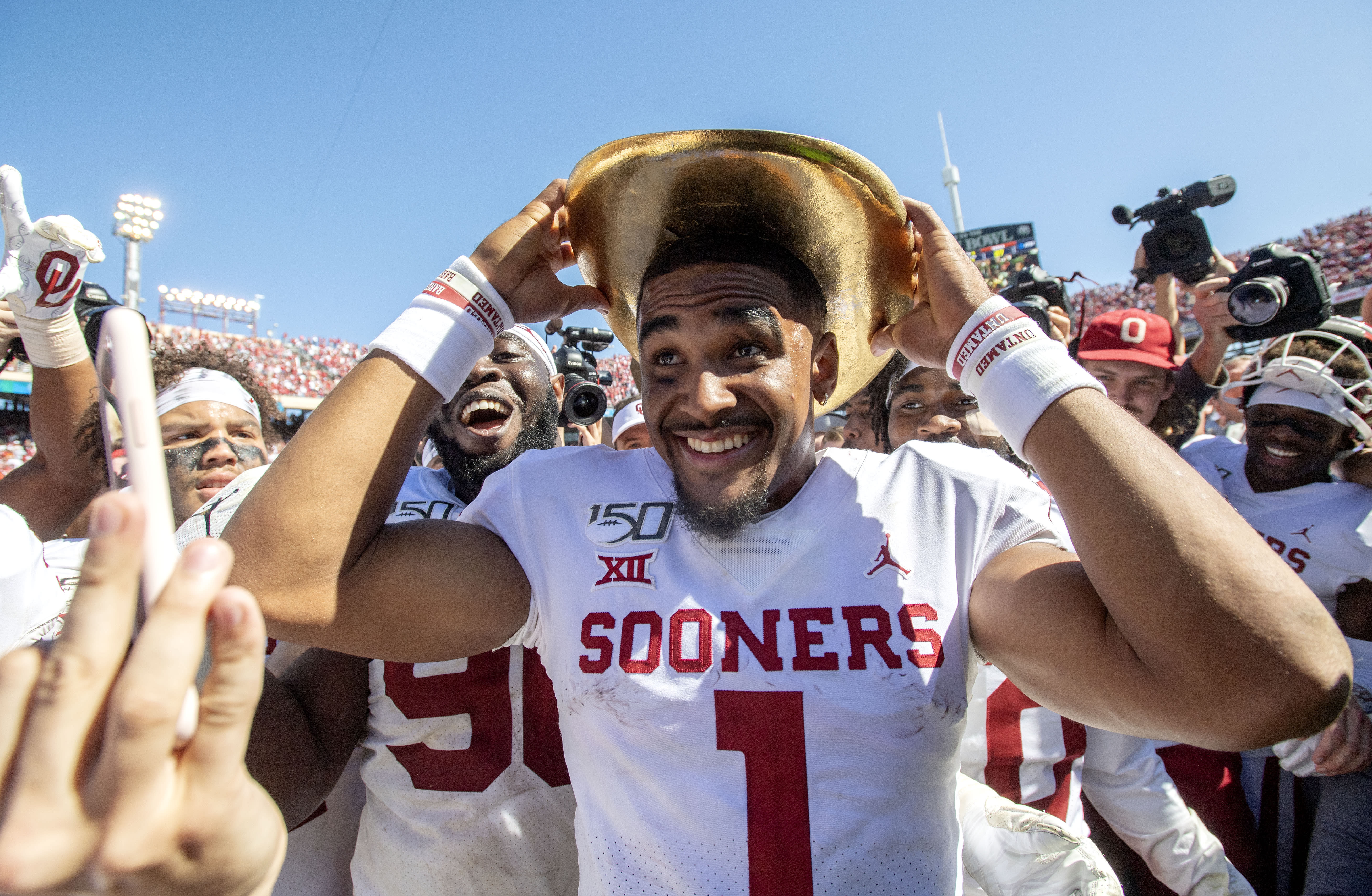 Oklahoma quarterback Jalen Hurts (1) puts on the Golden Hat after beating Texas 34-27 in an NCAA college football game at the Cotton Bowl, Saturday, Oct. 12, 2019, in Dallas. (AP Photo/Jeffrey McWhorter)