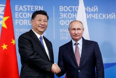Russian President Putin shakes hands with Chinese President Xi Jinping during their meeting on the sidelines of the Eastern Economic Forum in Vladivostok