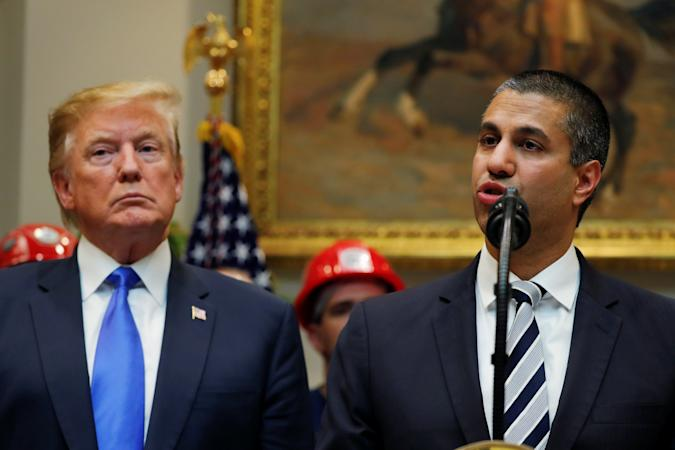U.S. President Donald Trump looks on as Federal Communications Commission (FCC)  Commissioner Ajit Pai speaks about on United States 5G deployment in the Roosevelt Room of the White House in Washington, U.S., April 12, 2019. REUTERS/Carlos Barria