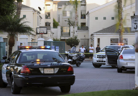 A Police Vehicle And Residents Are Seen At The Crime Scene Where Mayor Of Bell  Gardens