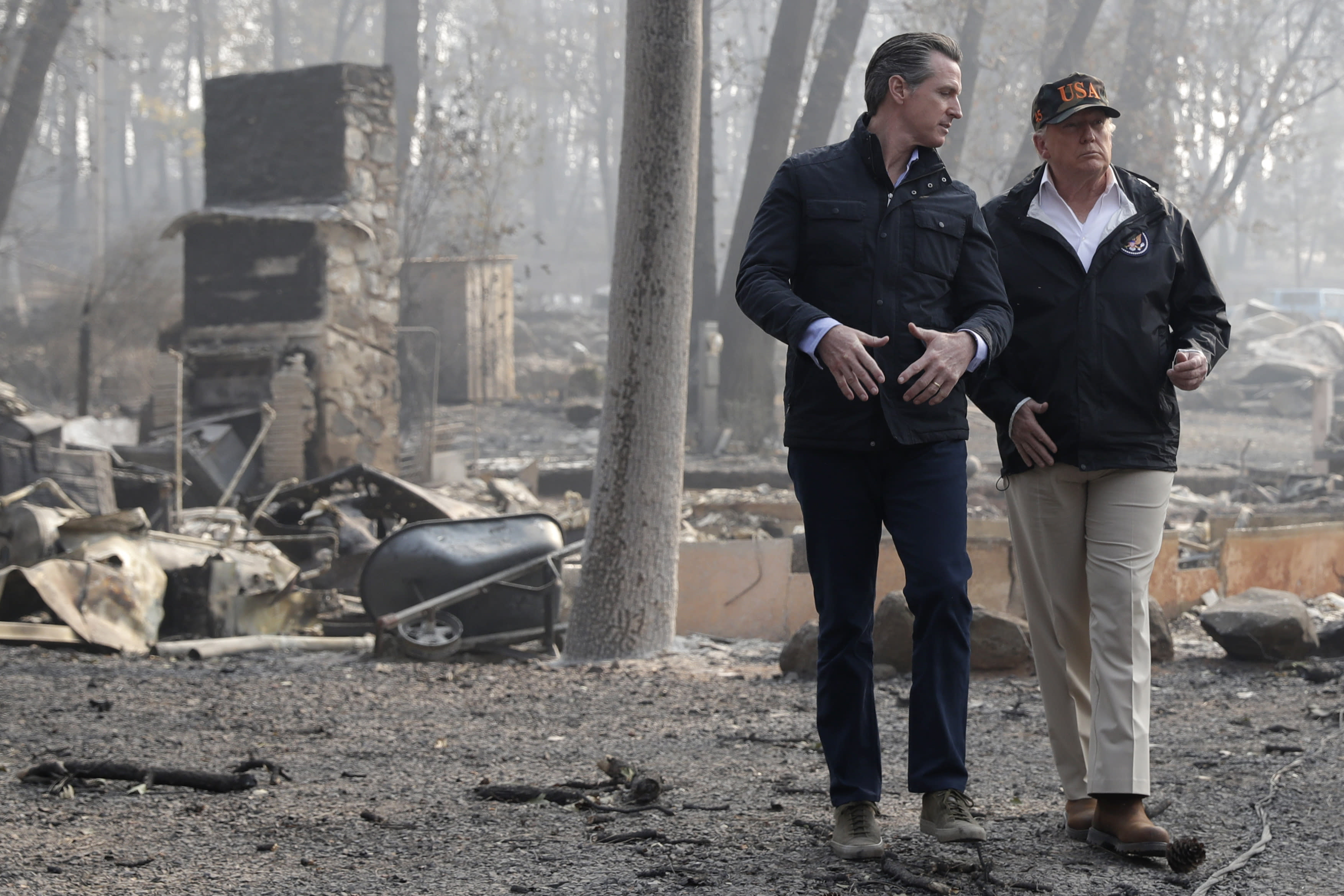 FILE - In this Nov. 17, 2018, file photo, President Donald Trump talks with California Gov.-elect Gavin Newsom during a visit to a neighborhood destroyed by the wildfires in Paradise, Calif. California has long used its status as the nation's most populous state (nearly 40 million people) and the world's fifth-largest economy (about $3 trillion) to pass trend-setting policies. But that role has crystallized in the Trump era, with California Democrats positioning the state as the nation's defense system against rollbacks of environmental and health care laws and the federal crackdown on illegal immigration, among other issues. First-year Gov. Gavin Newsom relishes his role as a Trump adversary and the leader of a state that does things before others. (AP Photo/Evan Vucci, File)
