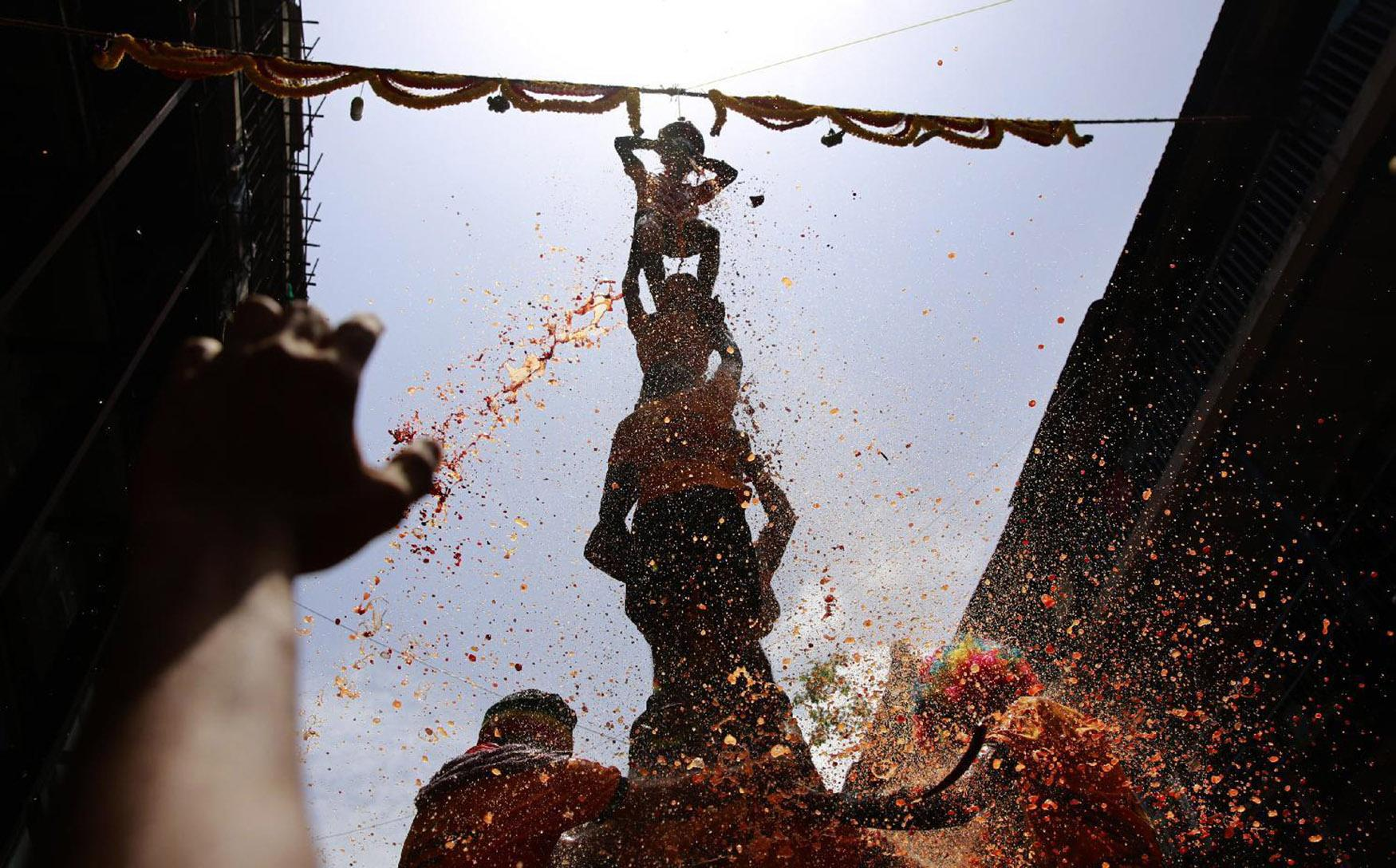 """<p>Curd spills as Indian devotees form a human pyramid and break the """"Dahi handi"""", an earthen pot filled with curd, as part of celebrations to mark Janmashtami in Mumbai, India, Aug. 25, 2016. The holiday marks the birth of Hindu god Krishna. (Photo: Rafiq Maqbool/AP) </p>"""