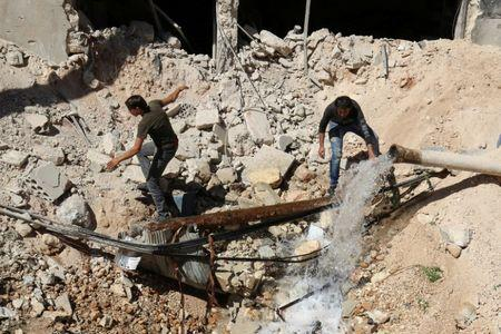 Men inspect a hole in the ground filled with water in a damaged site after airstrikes on the rebel held Tariq al-Bab neighbourhood of Aleppo, Syria September 24, 2016. REUTERS/Abdalrhman Ismail