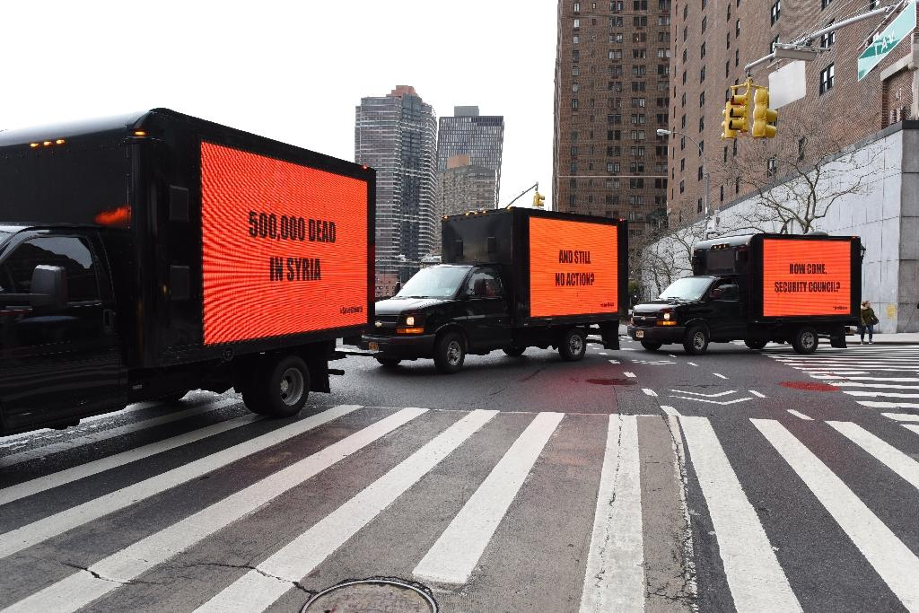 """Inspired by the Oscar-nominated film """"Three Billboards Outside Ebbing, Missouri"""", three billboards circle the United Nations on February 22, 2018 for three hours to demand action on Syria in advance of a Security Council vote in New York"""