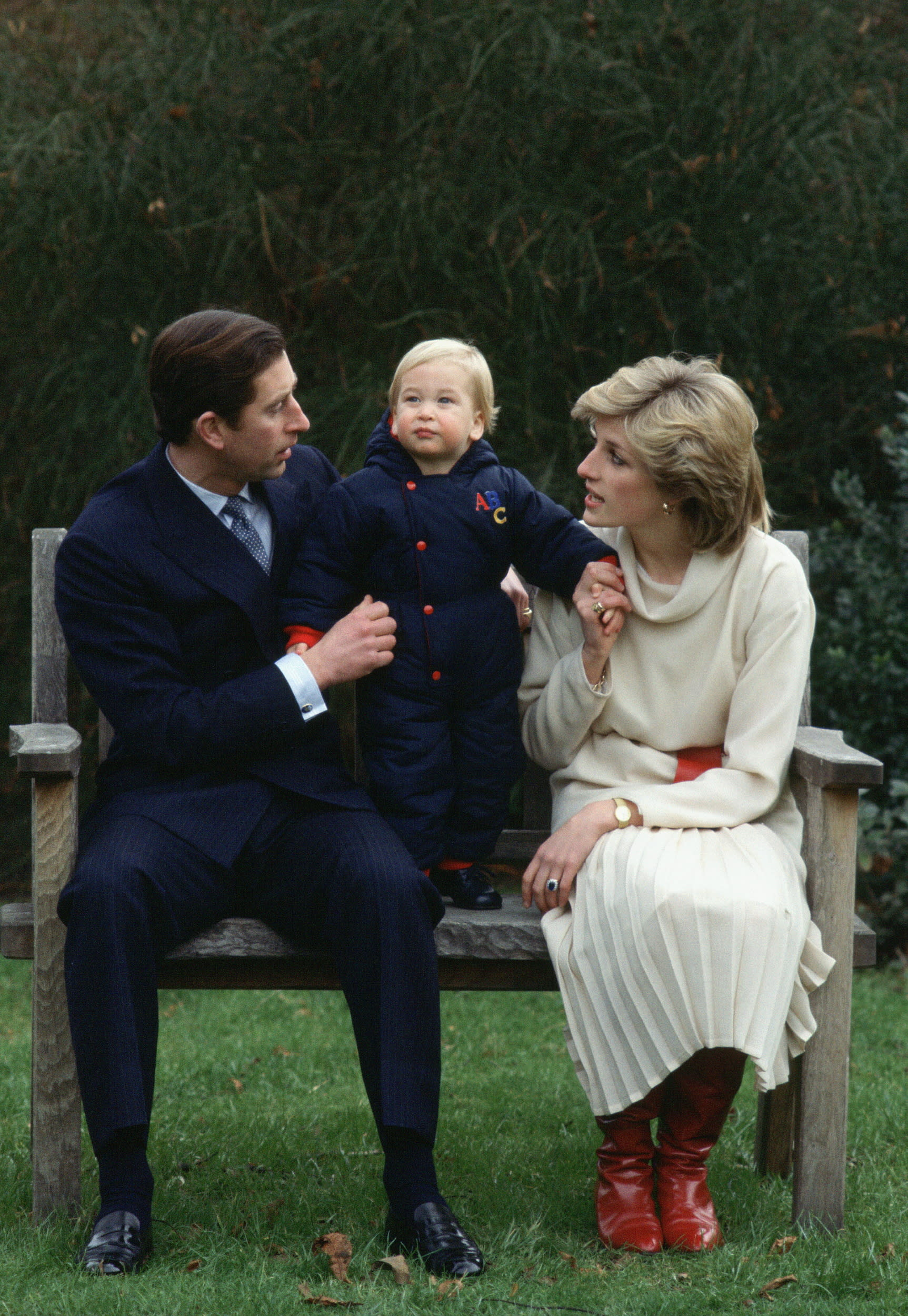 LONDON, UNITED KINGDOM - DECEMBER 14:  Prince Charles And Princess Diana Sitting On A Bench For A Photocall With Their Son, Prince William (age Approx 18 Months) , In Their Garden At Kensington Palace.  (Photo by Tim Graham/Getty Images)