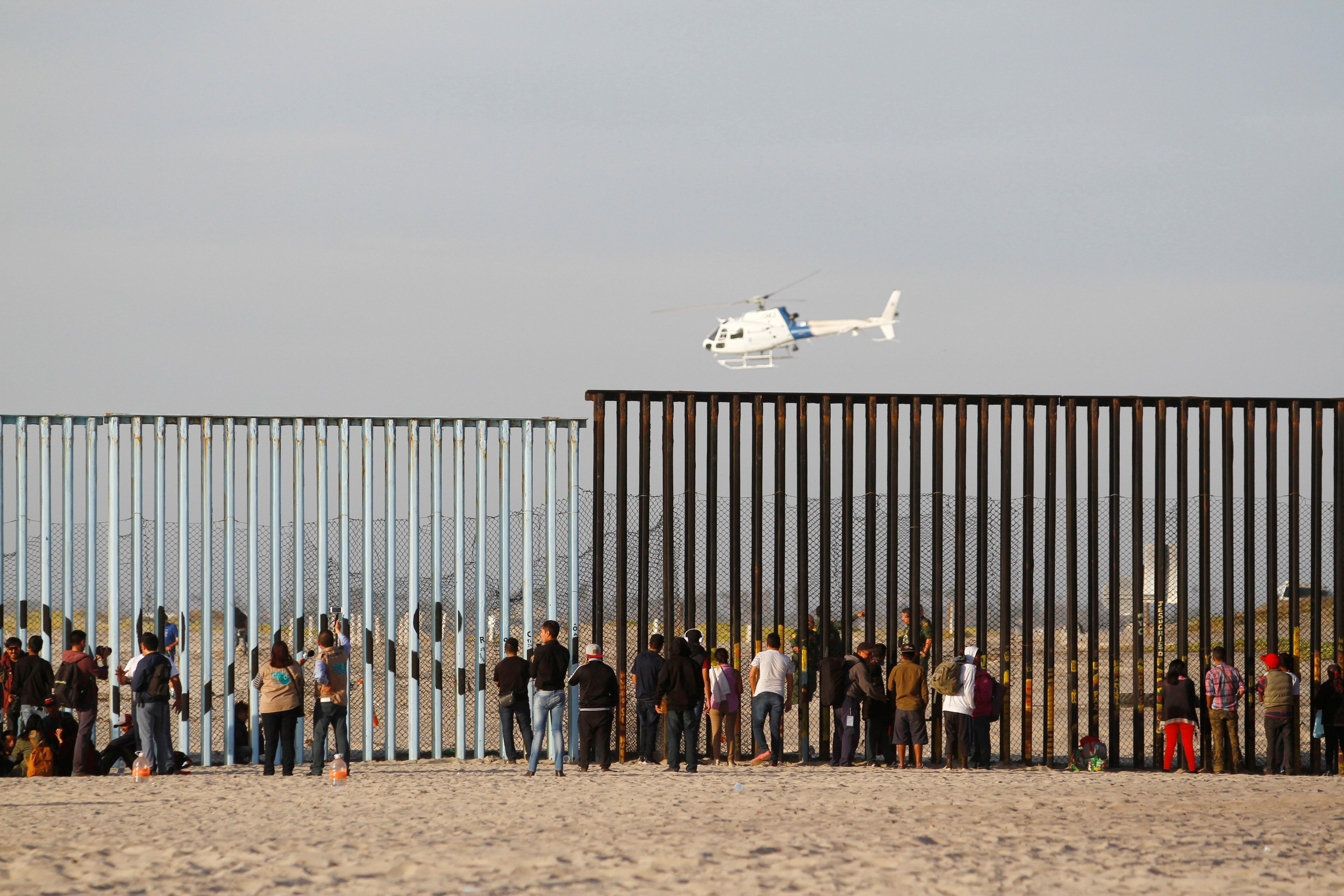 <p>Migrants, part of a caravan of thousands trying to reach the U.S., look through the border fence between Mexico and the United States after arriving in Tijuana, Mexico, Nov. 13, 2018. (Photo: Jorge Duenes/Reuters) </p>