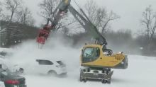 Watch Volvo excavator clear snowy cars in seconds with industrial blower