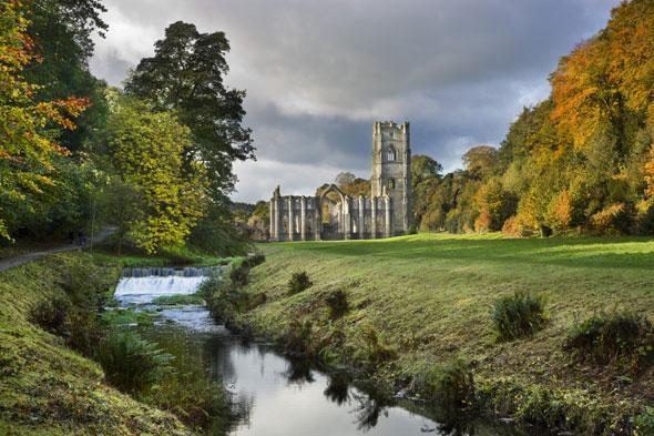 """<p> </p> <p class=""""p1""""> This World Heritage Site provides a stunning man-made contrast to the natural wonder of an autumnal landscape. Discover breathtaking views across the magnificent 12th century abbey ruins and the beautifully landscaped Georgian water garden, alongside seasonal shades in the surrounding 800 acres of beautiful countryside.</p>"""