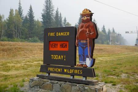 A Smokey the Bear sign warns of very high wildfire risk along the Seward Highway, near where the Swan Lake Fire near Seward