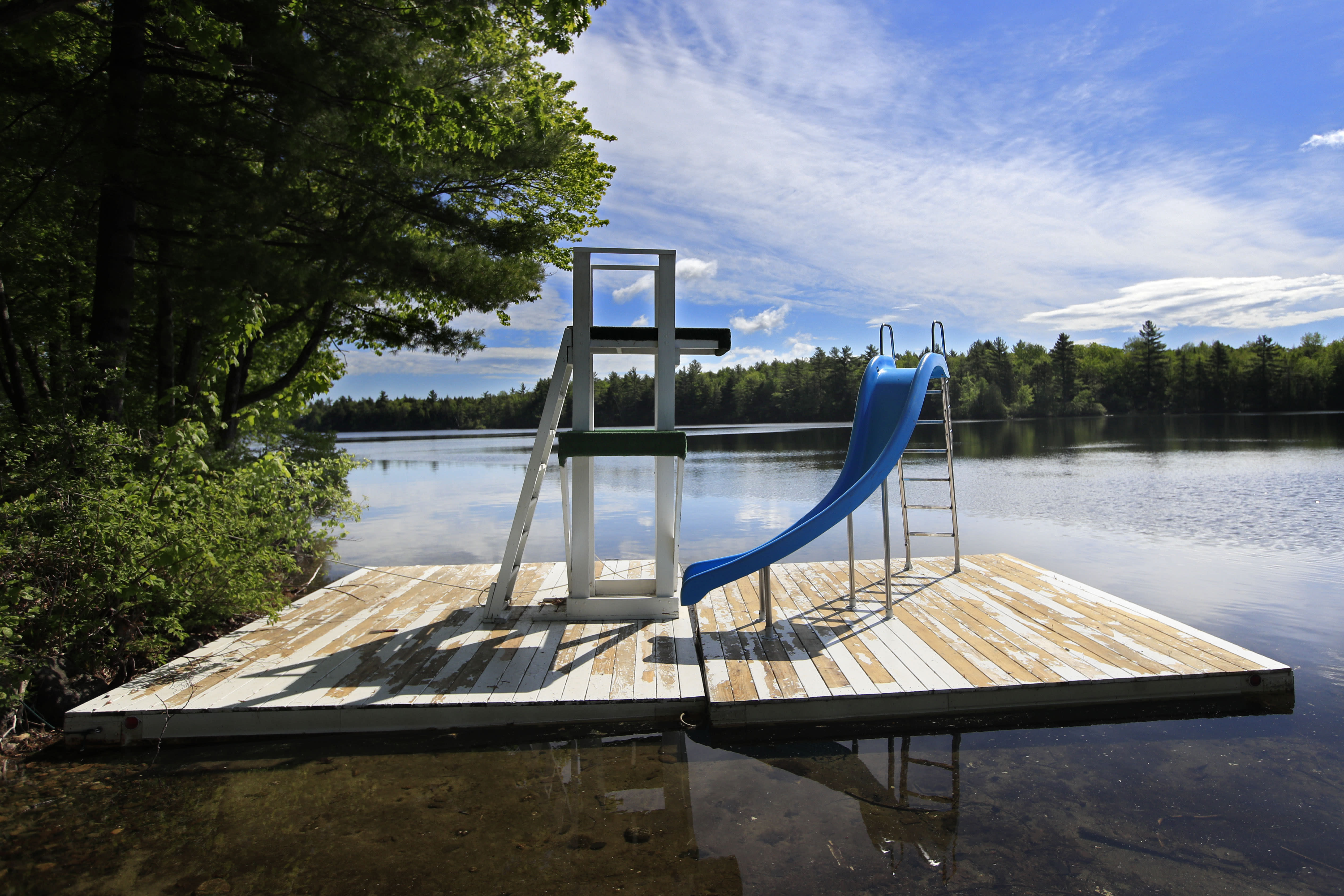 In this Thursday, June 4, 2020 photo, a slide on a floating dock is parked near the shore of Echo Lake at the the Camp Winnebago summer camp, in Fayette, Maine. The boys camp is going ahead with plans to open with a reduction in the number of campers and other changes to comply with guidelines for helping prevent the spread of the coronavirus. Many of the nation's 15,000-plus summer camps opting to close because of health concerns surrounding the pandemic, or because of delays in receiving rules or guidelines from licensing officials. (AP Photo/Robert F. Bukaty)