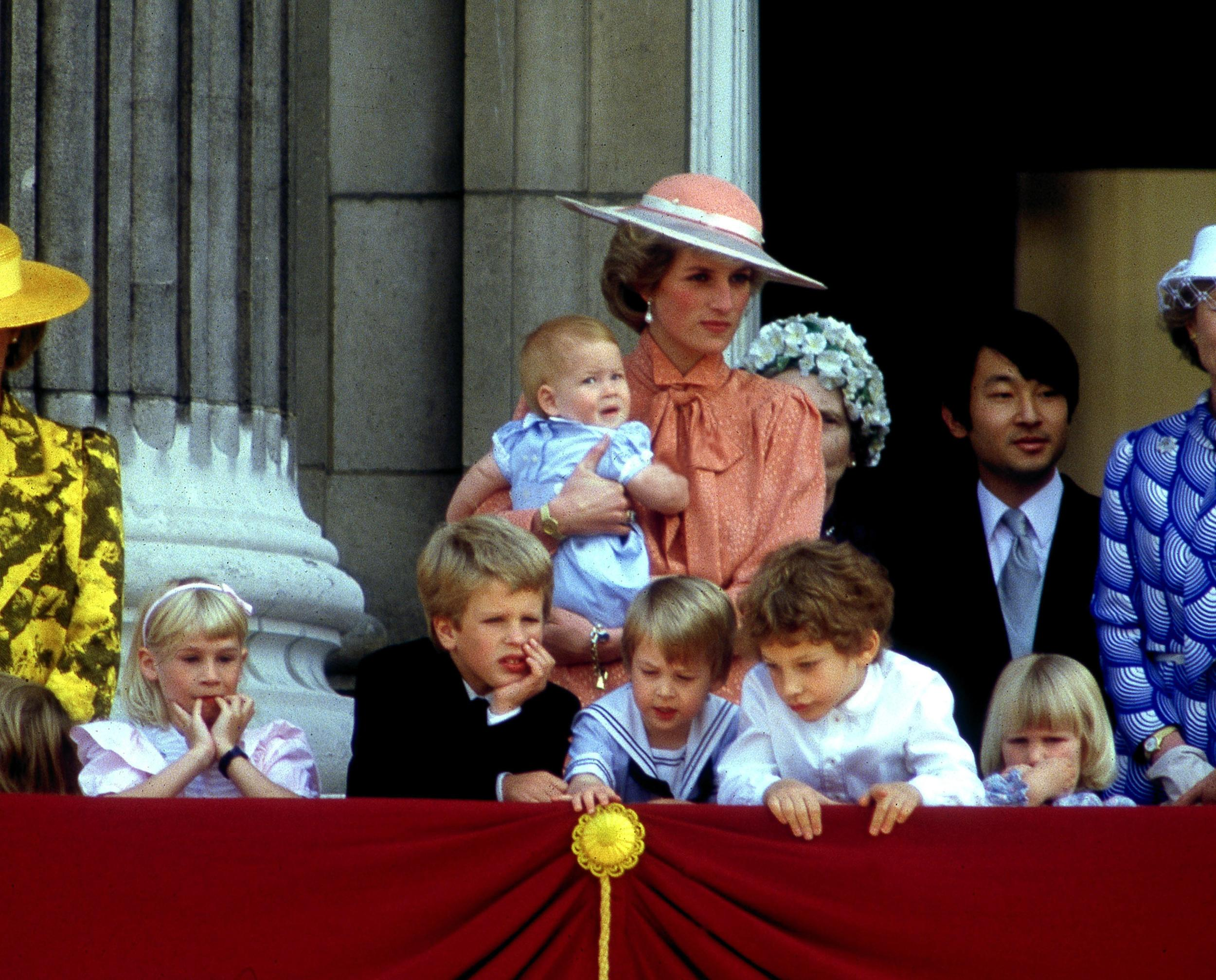 Princess Diana (1961 - 1997) holds her son Prince Harry as she watches the Trooping of the Colour from the balcony of Buckingham Palace, London, June 1985. On the right is Naruhito, Crown Prince of Japan. The children in the foreground are: (left to right) Lady Davina Windsor (now Lewis), Peter Phillips, Prince William, Lord Frederick Windsor and Lady Rose Windsor. (Photo by Jayne Fincher/Princess Diana Archive/Getty Images)