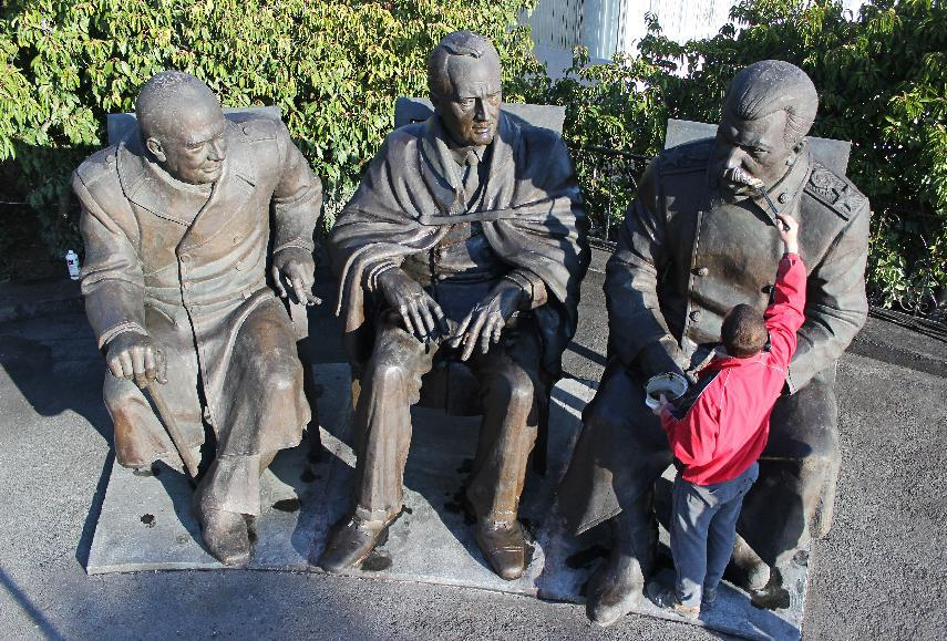 A sculptor assistant touches up a monument, featuring Soviet leader Josef Stalin (R), US President Theodore Roosevelt (C) and British Prime Minister Winston Churchill (AFP Photo/Yuri Lashov)